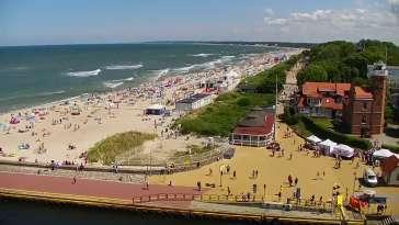Widok z pylonu na plażę, latarnię morską i kanał portowy.