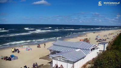 Piękna piaszczysta plaża w sezonie letnim oblegana przez spragnionych słońca turystów.