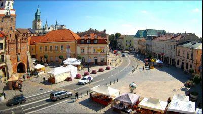 Kamera ustawiona jest na ulicę Królewską, z lewej strony prezentuje Bramę Krakowską a przed nią Plac Łokietka.