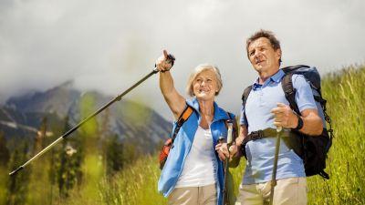 Zdjęcie na parę spacerujących po górach turystów.