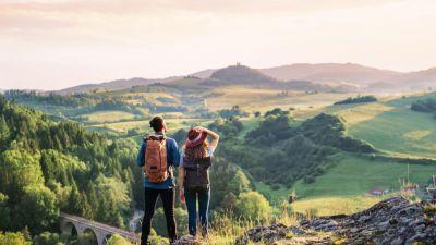 Zdjęcie na parę trekkingowców z plecakami turystycznymi z widokiem na góry.