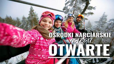 Widok na radosną i uśmiechniętą rodzinę narciarzy.