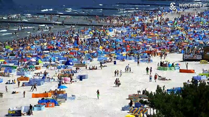 Plaża wŁebie pełna wypoczywających turystów.
