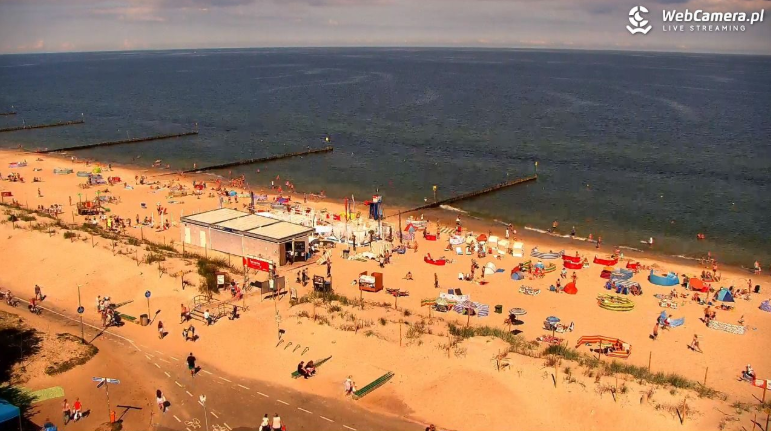 Ujęcie zkamery na plażowiczów wypoczywających wKołobrzegu
